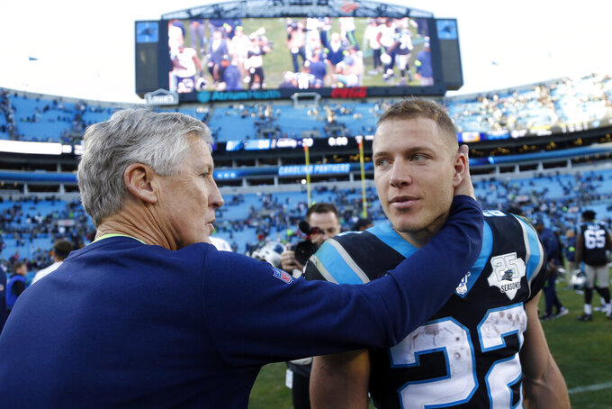 Seattle Seahawks head coach Pete Carroll hugs Carolina Panthers running back Christian McCaffrey (22) following an NFL football game in Charlotte, N.C., Sunday, Dec. 15, 2019. (AP Photo/Brian Blanco)