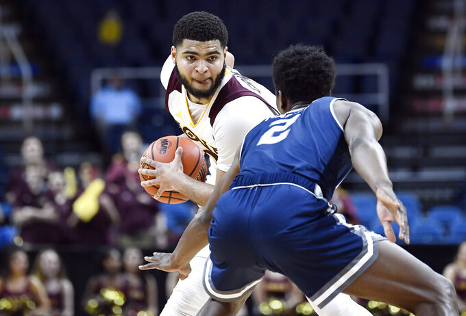 Iona guard E.J. Crawford, left, moves the ball against Monmouth forward Melik Martin during the first half of the championship NCAA college basketball game during the Metro Atlantic Athletic Conference tournament, Monday, March 11, 2019, in Albany, N.Y. (AP Photo/Hans Pennink)