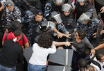 In this Friday Oct. 25, 2019,  MTV television reporter Nawal Berry, right, is protected by riot policemen after she was attacked by Shiite supporters of Hezbollah and Amal Movement groups during an anti-government protest, in Beirut, Lebanon. Lebanese journalists are facing wide-ranging harassment and obstacles to their work - including verbal insults and physical attacks, even death threats - amid reporting on nearly 50 days of anti-government protests, drawing into question Lebanon's reputation as a haven for free speech in a troubled region. (AP Photo/Hussein Malla)