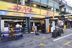 Technicians work around equipment and car parts in the The McLaren team pit at the Australian Formula One Grand Prix in Melbourne, Thursday, March 12, 2020. McLaren says it has withdrawn from the season-opening Australian Grand Prix in Melbourne after a team member tested positive for the coronavirus. (Michael Dodge/AAP Image via AP)