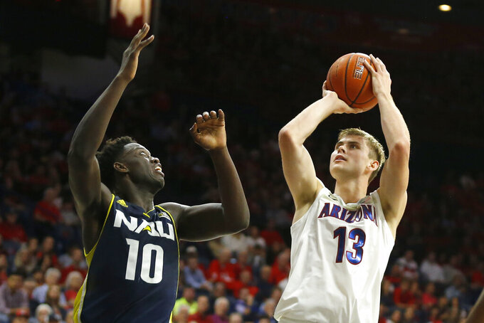 Arizona forward Stone Gettings (13) shoots over Northern Arizona forward Bernie Andre during the second half of an NCAA college basketball game Wednesday, Nov. 6, 2019, in Tucson, Ariz. (AP Photo/Rick Scuteri)