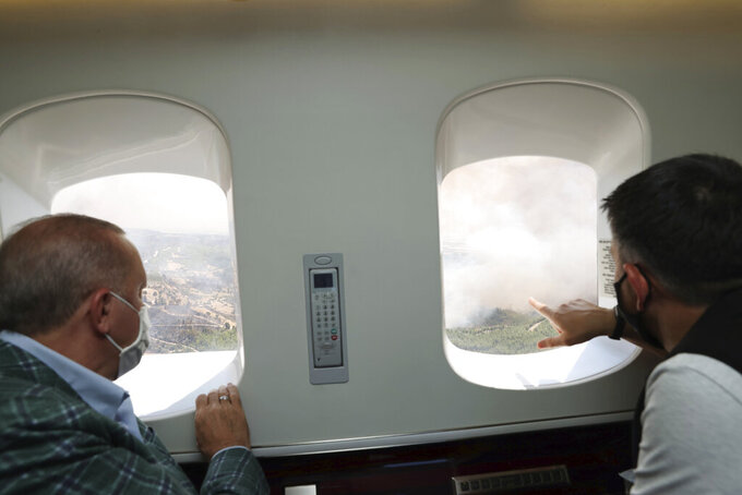 Turkey's President Recep Tayyip Erdogan, left, and Forestry Minister Bekir Pakdemirli watch from his plane the wildfires in Manavgat, Antalya, Turkey, Saturday, July 31, 2021. The death toll from wildfires raging in Turkey's Mediterranean towns rose to six Saturday after two forest workers were killed, the country's health minister said. Fires across Turkey since Wednesday burned down forests, encroaching on villages and tourist destinations and forcing people to evacuate.(Turkish Presidency via AP, Pool)