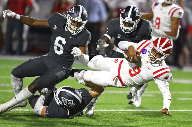 FILE - In this Friday, Oct. 25, 2019, file photo, Mater Dei quarterback Bryce Young is tackled after scrambling out of the pocket during a high school football game against St. John Bosco in Bellflower, Calif. Aside from being 2,000 miles away from his home in Southern California, the most challenging part of Alabama freshman quarterback Bryce Young's transition to college was dealing with two straight weeks of rainy weather in Tuscaloosa this winter. They don't get that in Pasadena, California. Otherwise, he's been too busy to be homesick. (Scott Varley/The Orange County Register via AP, File)