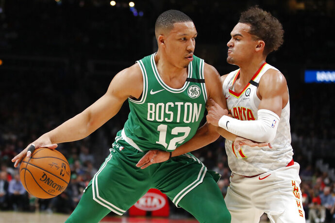 Boston Celtics forward Grant Williams (12) drives to the basket against Atlanta Hawks guard Trae Young (11) in the first half of an NBA basketball game on Monday, Feb. 3, 2020, in Atlanta. (AP Photo/Todd Kirkland)