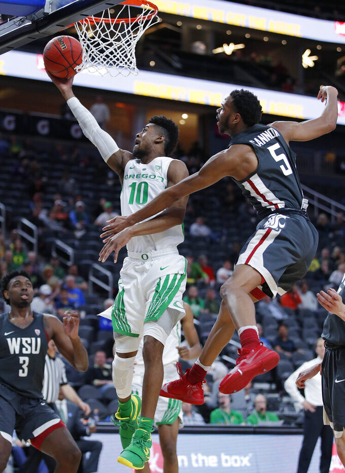Oregon's Victor Bailey Jr. shoots next to Washington State's Marvin Cannon during the second half of an NCAA college basketball game in the first round of the Pac-12 men's tournament Wednesday, March 13, 2019, in Las Vegas. (AP Photo/John Locher)