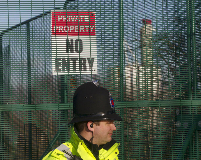 FILE - In this file photo dated Monday, Jan. 13, 2014, a policeman stands outside the entrance to the fracking drill site near Manchester, England.  The Cuadrilla company temporarily suspended fracking drilling for shale gas Friday Oct. 26, 2018, when a mild 0.8-magitude earthquake was detected, after fracking started on Oct. 15 for the first time since 2011. (AP Photo/Jon Super, FILE)