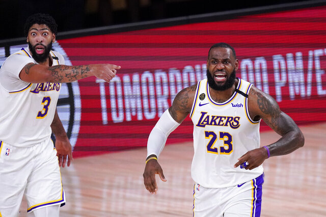 Los Angeles Lakers' LeBron James, right, and Anthony Davis argue a call during the first half of an NBA conference semifinal playoff basketball gameagainst the Houston Rockets Saturday, Sept. 12, 2020, in Lake Buena Vista, Fla. (AP Photo/Mark J. Terrill)
