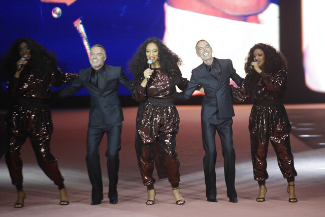 Designers Dean Caten and Dan Caten accept applause as they are joined by members of the band Sister Sledge, at the end of the Dsquared2 men's Fall-Winter 2020/21 collection, that was presented in Milan, Italy, Friday, Jan. 10, 2019. (AP Photo/Luca Bruno)