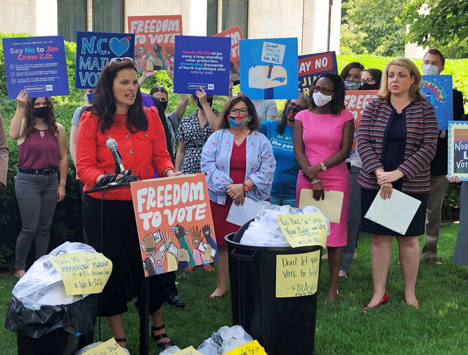 Allison Riggs, co-executive director of the Southern Coalition for Social Justice, at podium, speaks at a news conference outside the Legislative Building in Raleigh, N.C., Monday, June 14, 2021. Riggs and other speakers criticized three election bills advanced by state Senate Republicans, including one that would require mail-in absentee ballots be received by mail or handed in by 5 p.m. of the date of the election in order to count (AP Photo/Gary D. Robertson)