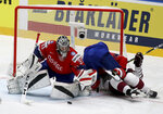 Norway's goalkeeper Henrik Haukeland, left, checks Erlend Lesund and Latvia's Teodors Blugers, right during the Ice Hockey World Championships group B match between Norway and Latvia at the Ondrej Nepela Arena in Bratislava, Slovakia, Tuesday, May 21, 2019. (AP Photo/Ronald Zak)