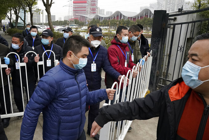 Security personnel move a barrier to clear the way for the World Health Organization team as they depart from the Wuhan Jinyintan Hospital after a field visit in Wuhan in central China's Hubei province on Saturday, Jan. 30, 2021. The World Health Organization team investigating the origins of the coronavirus pandemic visited another Wuhan hospital that had treated early COVID-19 patients on their second full day of work on Saturday. (AP Photo/Ng Han Guan)