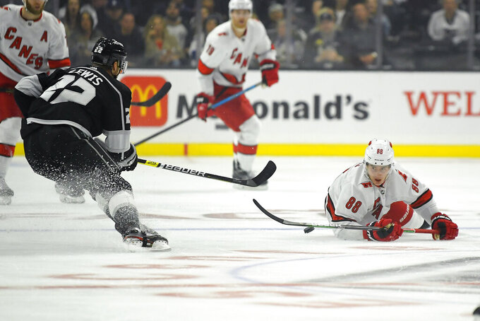 Carolina Hurricanes center Martin Necas, right, falls while trying to pass the puck as Los Angeles Kings center Trevor Lewis defends during the first period of an NHL hockey game Tuesday, Oct. 15, 2019, in Los Angeles. (AP Photo/Mark J. Terrill)