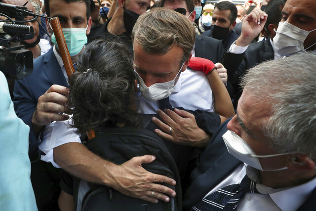 French President Emmanuel Macron, hugs a woman as he visits the Gemayzeh neighborhood, which suffered extensive damage from an explosion on Tuesday that hit the seaport of Beirut, Lebanon, Thursday, Aug. 6, 2020. (AP Photo/Bilal Hussein)