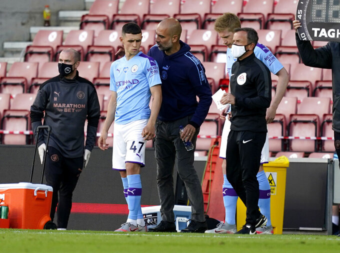 Manchester City's head coach Pep Guardiola talks with substitute player Phil Foden during the English Premier League soccer match between Southampton and Manchester City at St. Mary's Stadium in Southampton, England, Sunday, July 5, 2020. (AP Photo/Will Oliver,Pool)
