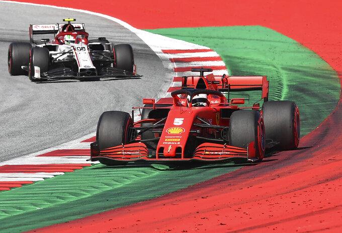 Ferrari driver Sebastian Vettel of Germany steers his car followed by Alfa Romeo driver Antonio Giovinazzi of Italy during the Austrian Formula One Grand Prix at the Red Bull Ring racetrack in Spielberg, Austria, Sunday, July 5, 2020. (Joe Klamar/Pool via AP)