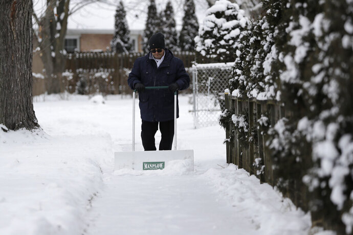 A man shovels the sidewalk of his house in Wheeling, Ill., Thursday, Feb. 13, 2020. Temps are falling into single digits in the evening and bottom- out at zero or below early Friday. (AP Photo/Nam Y. Huh)