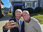 Former U.S. Vice President Joe Biden takes a selfie with Paul McGloin while visiting his childhood home in Scranton Pa., on Wednesday, Oct. 23, 2019. (Jason Farmer/The Times-Tribune via AP)