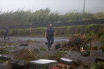 Portuguese coastguard officers walk among debris blocking a road in the seafront village of Feteira, outside Horta, in the Portuguese island of Faial, Wednesday, Oct. 2, 2019. Hurricane Lorenzo is lashing the mid-Atlantic Azores Islands with heavy rain, powerful winds and high waves. The Category 2 hurricane passed the Portuguese island chain Wednesday. (AP Photo/Joao Henriques)