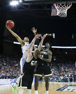 Kentucky's Keldon Johnson, left, shoots over Wofford's Matthew Pegram (50) and Tray Hollowell, right, during the first half of a second-round game in the NCAA men's college basketball tournament in Jacksonville, Fla., Saturday, March 23, 2019. (AP Photo/John Raoux)