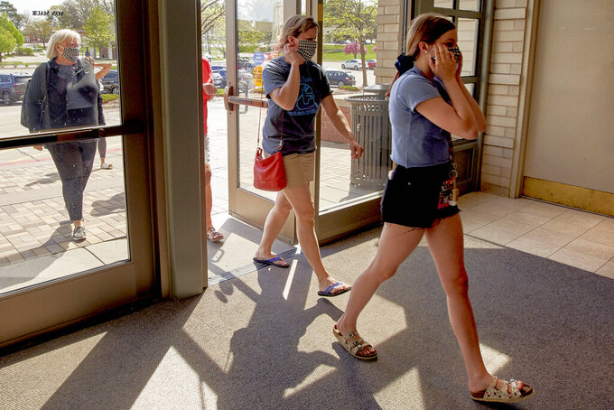 Shoppers with face masks enter the Von Maur department store in Omaha, Neb., Friday, May 1, 2020. The Von Maur stores opened for the first time since measures to combat the spread of the coronavirus were put in place. (AP Photo/Nati Harnik)