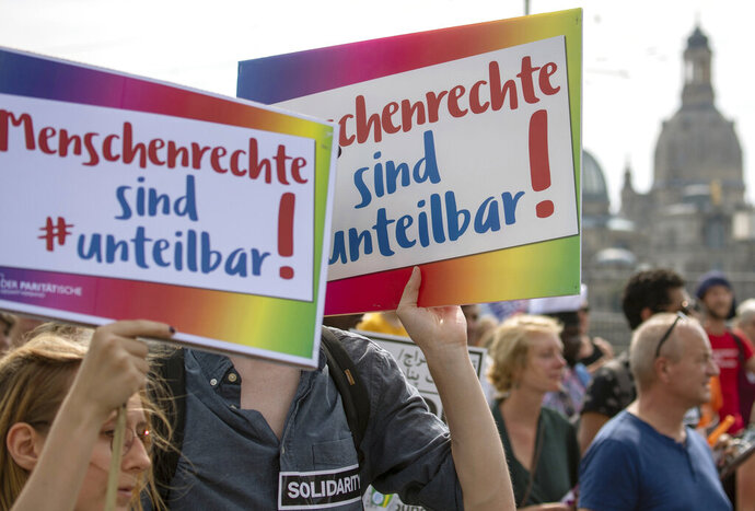 People take part in a protest rally of the 'Unteilbar' (individable) movement for democracy and human rights in Dresden, Germany, Aug. 24, 2019. Slogan reads 'Human Rights are Individable'. (Robert Michael/dpa via AP)