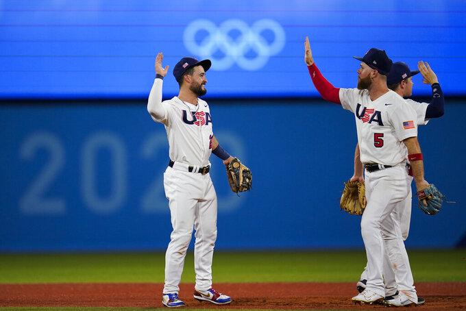United States' Eddy Alvarez, center, and Eric Filia celebrate after a semi-final baseball game against South Korea at the 2020 Summer Olympics, Thursday, Aug. 5, 2021, in Yokohama, Japan. The United States won 7-2. (AP Photo/Sue Ogrocki)