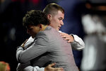 Number one overall pick Henry Davis, right, is embraced after being selected by Pittsburgh Pirates in the first round of the 2021 MLB baseball draft, Sunday, July 11, 2021, in Denver. (AP Photo/David Zalubowski)