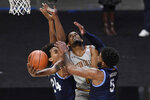 Boston College's Wynston Tabbs, center, is fouled by Villanova's Justin Moore (5) while making a basket as Villanova's Jeremiah Robinson-Earl (24) defends during the second half of an NCAA college basketball game, Wednesday, Nov. 25, 2020, in Uncasville, Conn. (AP Photo/Jessica Hill)