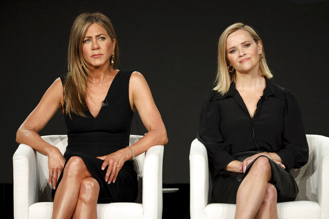 Jennifer Aniston, left, and Reese Witherspoon speak at