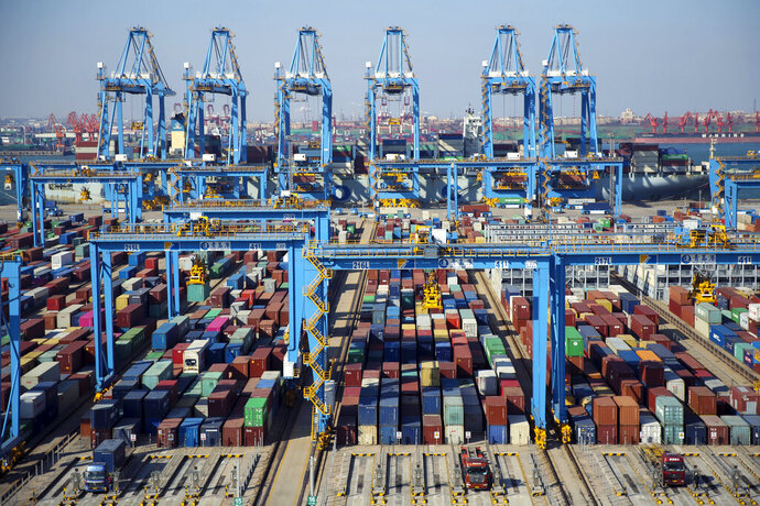 In this Thursday, Nov. 28, 2019, photo, trucks load containers at the automated container dockyard in Qingdao in east China's Shandong province. A Chinese official newspaper has reiterated, repeatedly, Beijing's demand that the U.S. roll back tariffs imposed by President Donald Trump's administration in exchange for a deal. The Communist Party newspaper Global Times ran several articles Monday, Dec. 2, 2019 that emphasized there would be no deal without a promise to phase out the tariffs imposed by Washington. (Chinatopix via AP)