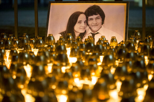 FILE - In this Wednesday, Feb. 28, 2018 file photo, light tributes are seen during a silent protest in memory of murdered journalist Jan Kuciak and his girlfriend Martina Kusnirova, seen in photo, in Bratislava, Slovakia. The state prosecutor in Slovakia requested on Thursday, July 23, 2020 a 25-year prison term for all three defendants in the alleged contract killings of an investigative journalist and his fiancee, a case that triggered a political crisis and brought down the country's government.   (AP Photo/Bundas Engler, file)