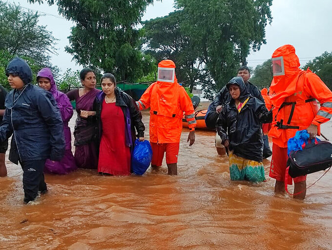 This photograph provided by India's National Disaster Response Force (NDRF) shows NDRF personnel rescuing people stranded in floodwaters in Chikhali, in the western Indian state of Maharashtra, Friday, July 23, 2021. Landslides triggered by heavy monsoon rains hit parts of western India, killing more than 30 people and leading to the overnight rescue of more than 1,000 other people trapped by floodwaters, officials said Friday.(National Disaster Response Force via AP)