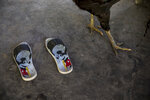 In this Sept. 2, 2019 photo, a chicken walks past a pair of Mickey Mouse flip flops, in the Ka 'a kyr village, Para state, Brazil. Daily life in the remote Tembe indigenous villages in the Amazon jungle of Brazil mixes tradition and modernity. (AP Photo/Rodrigo Abd)