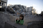 A Palestinian boy stands next to the rubble of Hamas' Al-Aqsa TV station building which was hit by Israeli airstrikes on Monday, in Gaza City, Tuesday, Nov. 13, 2018. (AP Photo/Khalil Hamra)