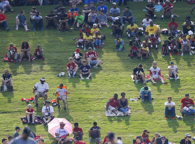 File-This July 27, 2017, file photo shows Atlanta Falcons fans watching during NFL football training camp in Flowery Branch, Ga. The Atlanta Falcons have cleared out of their practice facility and given the keys to the Los Angeles Rams for the week. The Falcons are determined to be good hosts to the Rams, who are using the facility as their practice site for Sunday's Super Bowl 53. (AP Photo/John Bazemore, File)