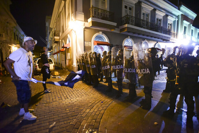 Demonstrators stand in front of riot control units during clashes in San Juan, Puerto Rico, Monday, July 22, 2019. Protesters are demanding Gov. Ricardo Rossello step down following the leak of an offensive, obscenity-laden online chat between him and his advisers that triggered the crisis. (AP Photo / Carlos Giusti)