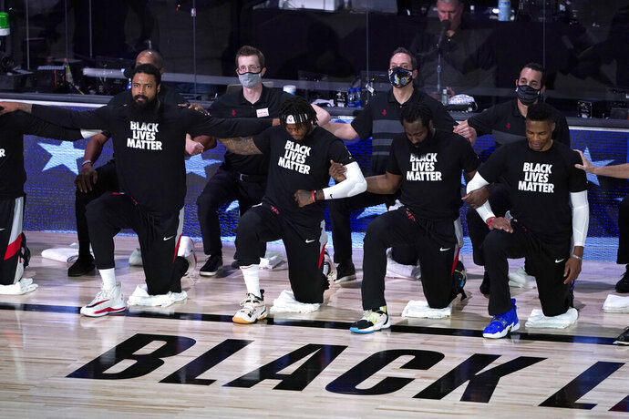 Houston Rockets, from left to right, Tyson Chandler, Ben McLemore, James Harden and Russell Westbrook knell during the national anthem before an NBA basketball first round playoff game against the Oklahoma City Thunder Saturday, Aug. 29, 2020, in Lake Buena Vista, Fla. (AP Photo/Ashley Landis)