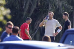 Tampa Bay Buccaneers quarterback Tom Brady takes a drink as unidentified individuals are seen near him during a private workout, Tuesday, June 23, 2020 at Berkeley Preparatory School in Tampa, Fla. (Chris Urso/Tampa Bay Times via AP)