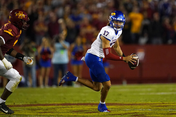 Kansas quarterback Jason Bean (17) runs from Iowa State defensive end Will McDonald IV (9) during the first half of an NCAA college football game, Saturday, Oct. 2, 2021, in Ames, Iowa. (AP Photo/Charlie Neibergall)