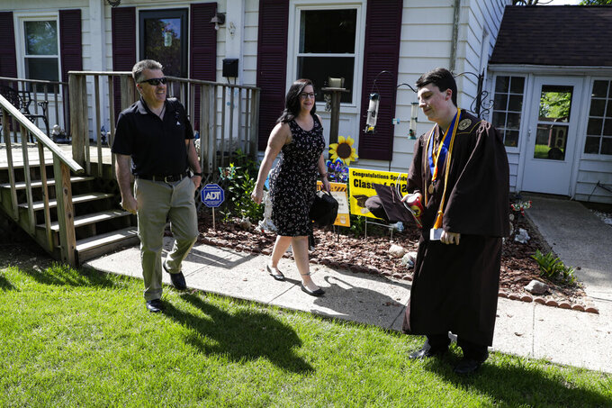 Jacob Foxworthy, right, and his parents Ted and Cindy Foxworthy leave their home to attend the Speedway High School graduation ceremony at the Indianapolis Motor Speedway in Indianapolis, Saturday, May 30, 2020. The ceremony was held at the track to allow for social distancing requirements due to the COVID-19 pandemic. When Ted Foxworthy was diagnosed with cancer, he set two goals: Celebrating his youngest child's 18th birthday and seeing him graduate. (AP Photo/Michael Conroy)