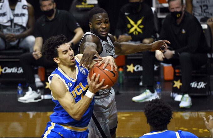 UCLA guard Jules Bernard (1)] and Oregon forward Eugene Omoruyi (2) battle for a rebound during the first half of an NCAA college basketball game Wednesday, March 3, 2021, in Eugene, Ore. (AP Photo/Andy Nelson)