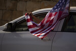 An Israeli supporter of U.S. President Donald Trump for re-election waves an American flag from her car as she headed for a rally outside of the U.S. Embassy, in Jerusalem, Tuesday, Oct. 27, 2020. (AP Photo/Maya Alleruzzo)