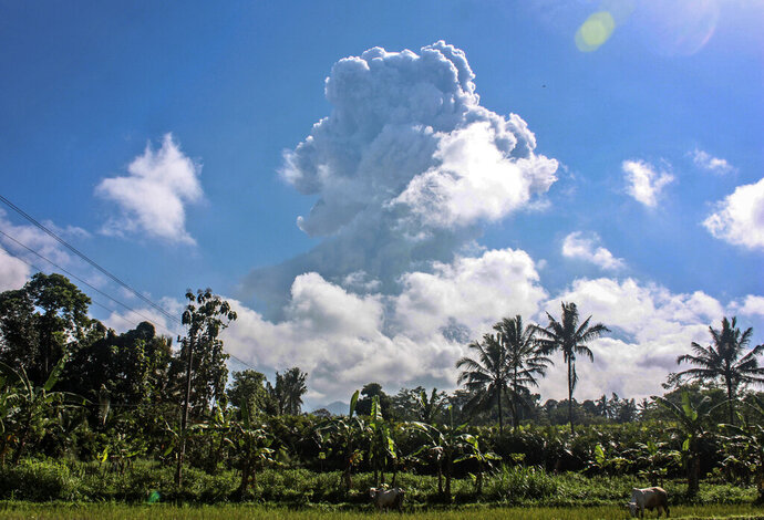 Mount Merapi spews volcanic materials during an eruption as seen from Sleman, Indonesia, Sunday, June 21, 2020. The country's most volatile volcano on Sunday spewed ash and hot gas in a massive column as high as 6 kilometers (3.7 miles) into the sky. Indonesia, an archipelago of 270 million people, is prone to earthquakes and volcanic activity because it sits along the Pacific