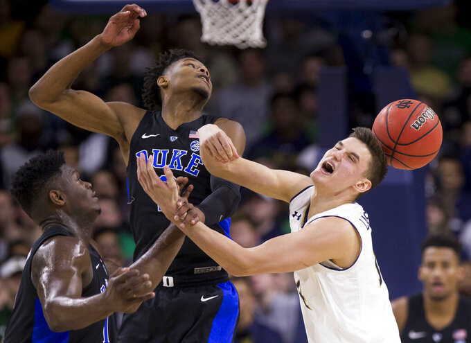 Duke's Zion Williamson, left, and Cam Reddish, center, compete for the ball with Notre Dame's Nate Laszewski (14) during the first half of an NCAA college basketball game Monday, Jan. 28, 2019, in South Bend, Ind. (AP Photo/Robert Franklin)