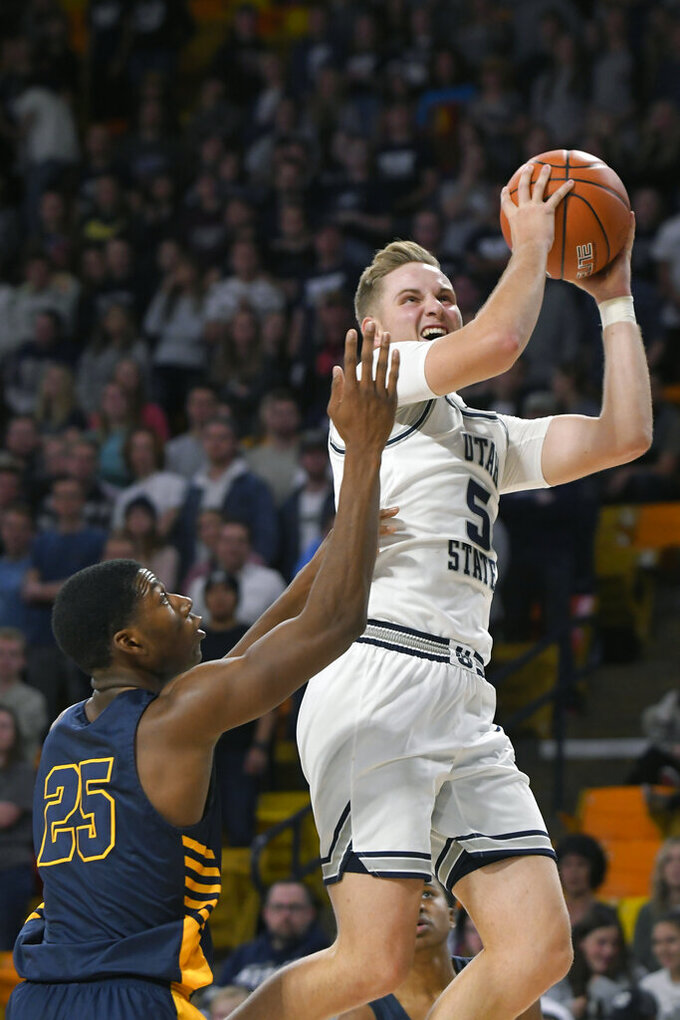 Utah State guard Sam Merrill (5) shoots as North Carolina A&T forward Webster Filmore (25) defends during the second half of an NCAA college basketball game Friday, Nov. 15, 2019, in Logan, Utah. (AP Photo/Eli Lucero)