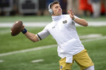 Notre Dame quarterback Ian Book (12) warms up before an NCAA college football game Saturday, Dec. 5, 2020, in South Bend, Ind. (Matt Cashore/Pool Photo via AP)