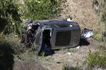 A vehicle rests on its side after a rollover accident involving golfer Tiger Woods along a road in the Rancho Palos Verdes suburb of Los Angeles on Tuesday, Feb. 23, 2021. Woods suffered leg injuries in the one-car accident and was undergoing surgery, authorities and his manager said. (AP Photo/Ringo H.W. Chiu)