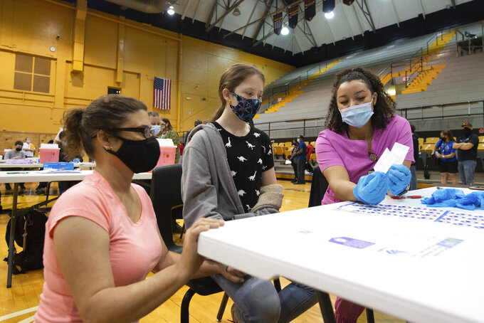 Eighth grader at Robinson Middle School, Jasic Helvey, 12, hears information about her COVID-19 vaccine Monday, May 17, 2021, at Topeka High School with by Shaunee Darrough, registered nurse with TrueCare Nursing, with her mom, Brandi Snyder, nearby. (Evert Nelson/The Topeka Capital-Journal via AP)