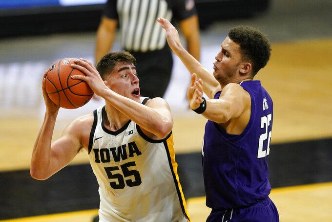Iowa center Luka Garza looks to shoot over Northwestern forward Pete Nance, right, during the second half of an NCAA college basketball game, Tuesday, Dec. 29, 2020, in Iowa City, Iowa. Iowa won 87-72. (AP Photo/Charlie Neibergall)