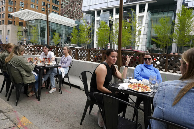 FILE - In this Sunday, May 2, 2021 file photo, patrons seated at outdoor tables at a restaurant converse and dine without masks, in Boston. Gov. Charlie Baker said Monday, May 17 that all remaining COVID-19 restrictions will be lifted in Massachusetts on Memorial Day weekend. Though face coverings will still be mandatory on public and private transportation systems - including rideshares, taxis, ferries, MBTA subways and busses, commuter rail and transportation stations, and in health care facilities and in other settings hosting vulnerable populations like congregate care settings. (AP Photo/Steven Senne, File)